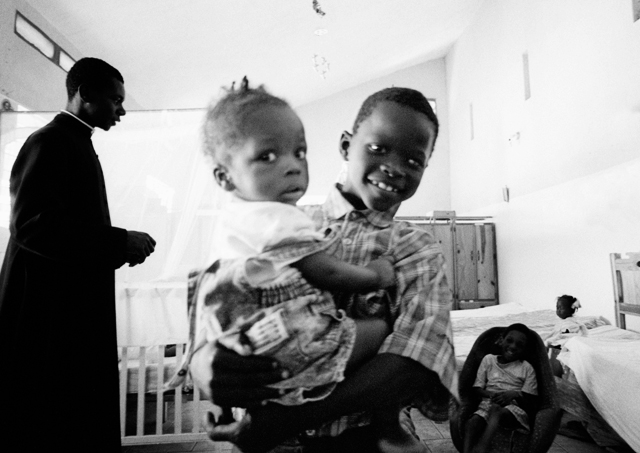 A boy holds a girl suffering from Sickle Cell Anemia at the orphanage