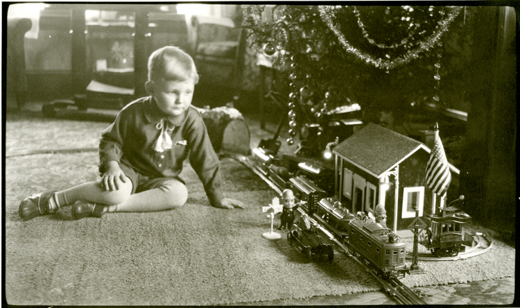 kid at Christmas with tree and model train, circa 1935